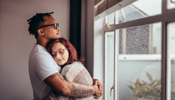 Interracial couple hugging near window Interracial couple hugging each other while standing near window. African man embracing his caucasian girlfriend at home. mixed race person stock pictures, royalty-free photos & images