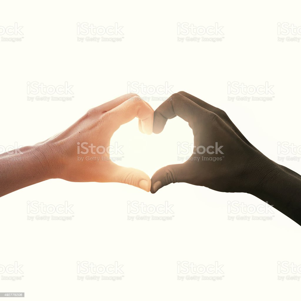 interracial couple in love heart shape hand gesture stock photo