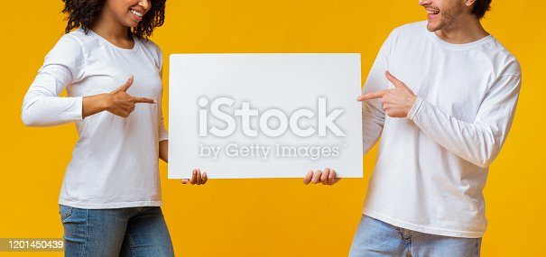 1159989540 istock photo Interracial Couple Pointing At White Advertisement Placard In Their Hands 1201450439