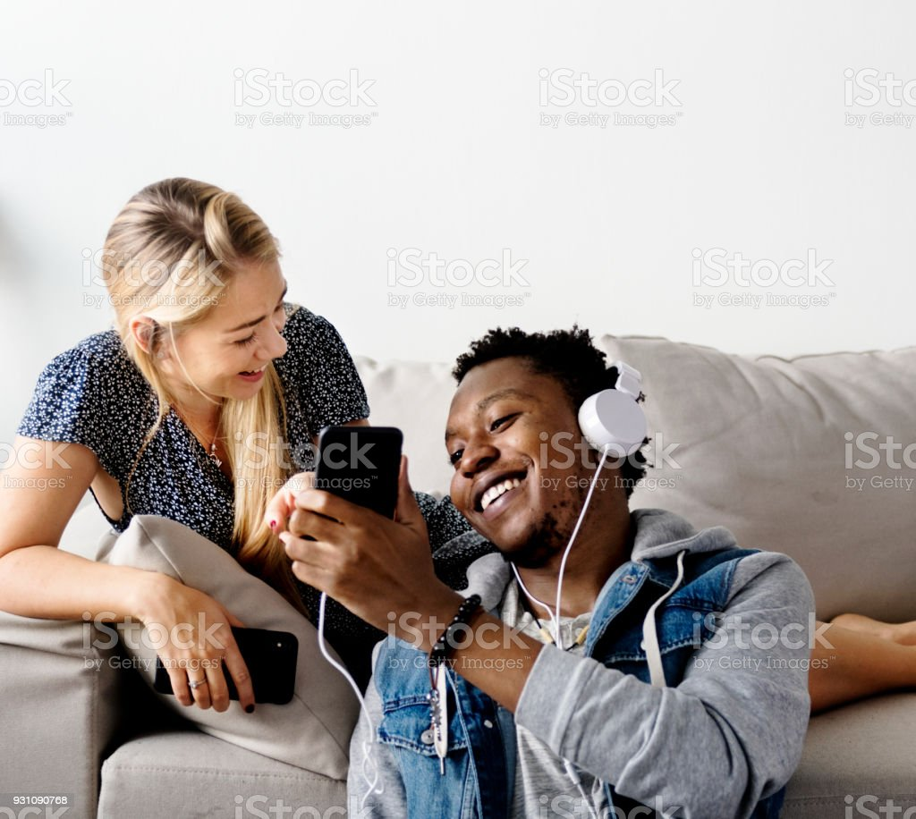 Interracial couple sharing music at home love, leisure and music concept stock photo