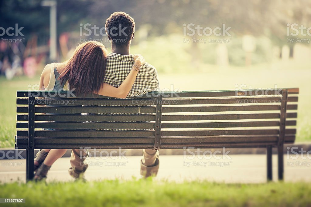Interracial Couple Sitting On A Park Bench Together Stock Photo