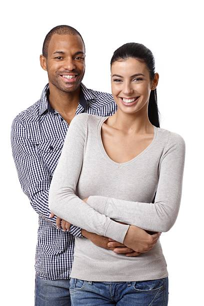 Interracial couple smiling and holding one another on white stock photo