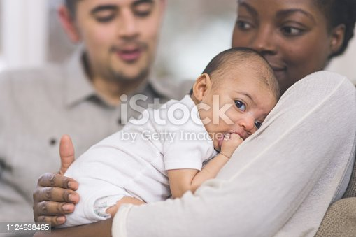 A beautiful young African American mother gently holds her infant girl to her chest. The baby has her hand in her mouth and her eyes are wide open. Dad has his arm around mom and is looking at her affectionately.