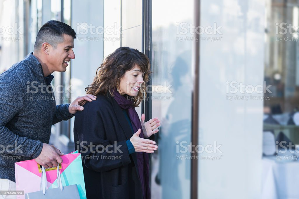 Interracial couple window shopping in city stock photo