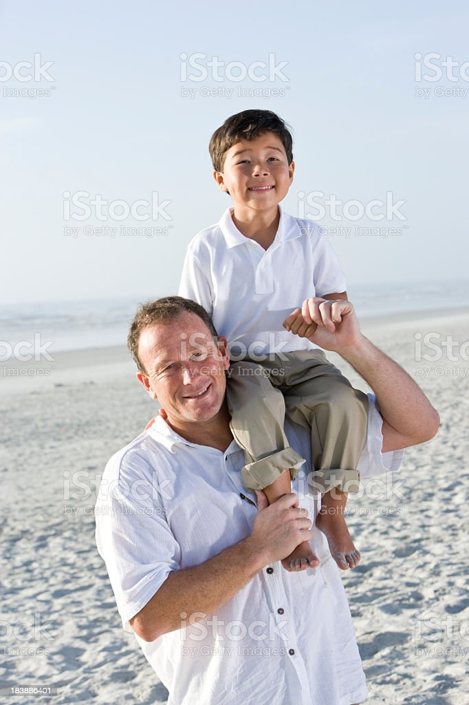 Interracial family, boy sitting on dad's shoulder at beach royalty-free stock photo