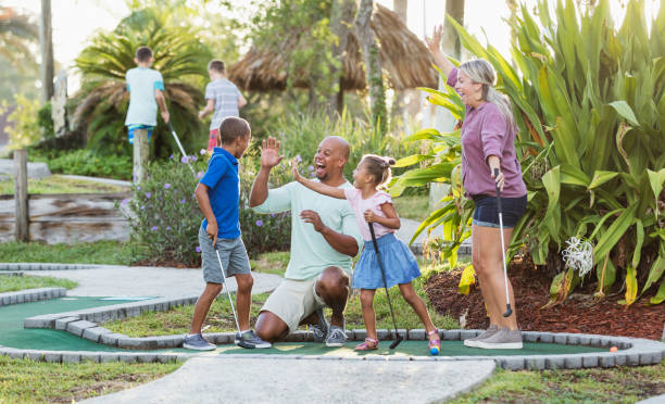 Interracial family, two children playing miniature golf stock photo