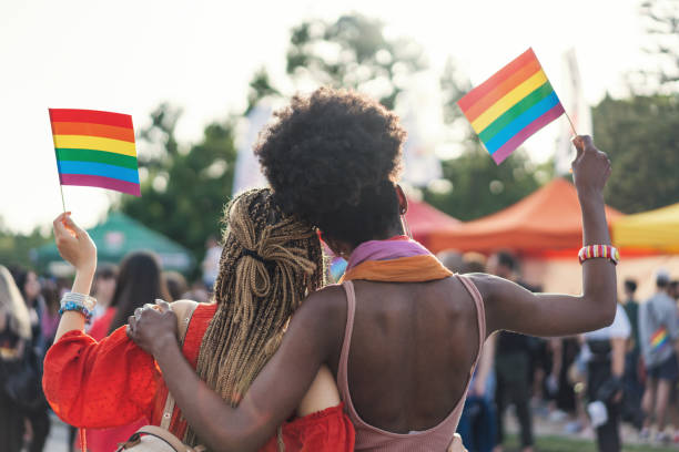 Interracial female couple waving rainbow flags at the pride parade stock photo