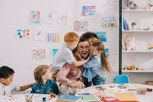 interracial kids hugging happy teacher at table in classroom interracial kids hugging happy teacher at table in classroom preschool age stock pictures, royalty-free photos & images