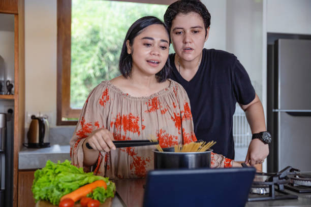 Interracial lesbian couple watching cooking tutorial from digital tablet Shot of interracial lesbian couple watching cooking tutorial from digital tablet cisgender stock pictures, royalty-free photos & images