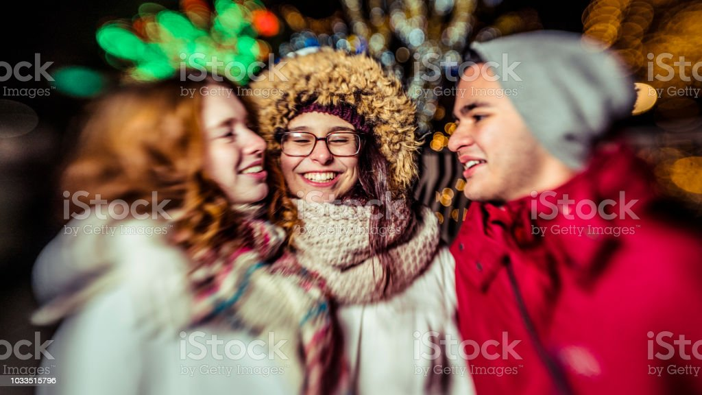 Interracial loving couple, teenagers, the beautiful Caucasian white 17-years-old long haired girl and handsome Latino Hispanic 18-years-old boy, and their friend, 15-years-old teenager girl, enjoying Christmas Illumination and having fun in the cold winte – zdjęcie