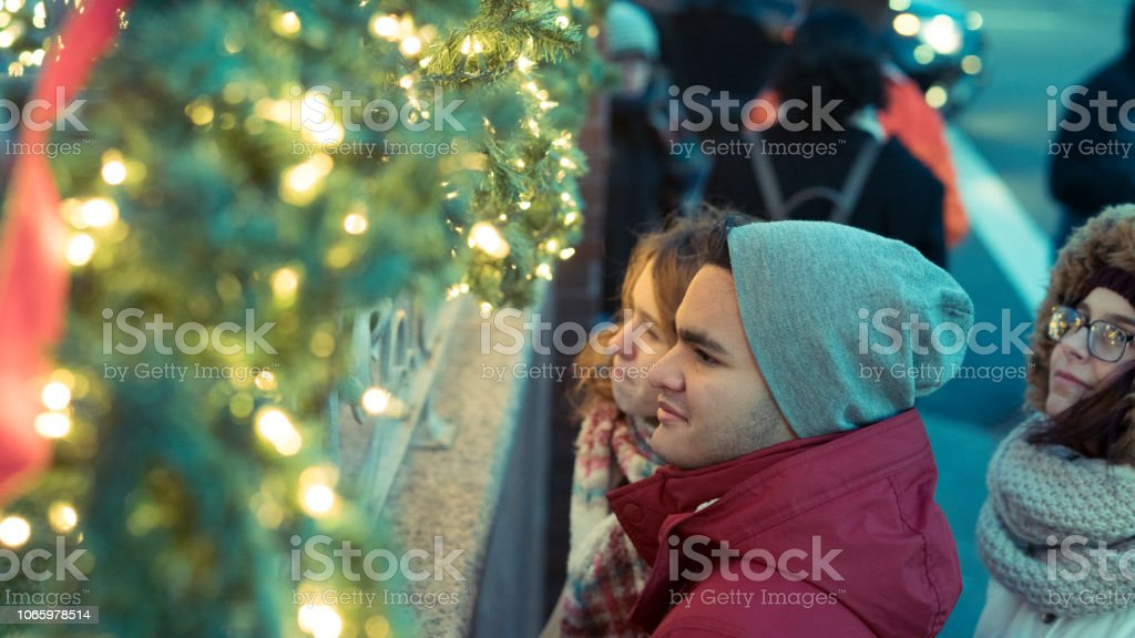 Interracial loving couple, teenagers, the beautiful Caucasian white 17-years-old long haired girl and handsome Latino Hispanic 18-years-old boy, and their friend, 15-years-old teenager girl, enjoying Christmas Illumination and having fun in the cold winte stock photo
