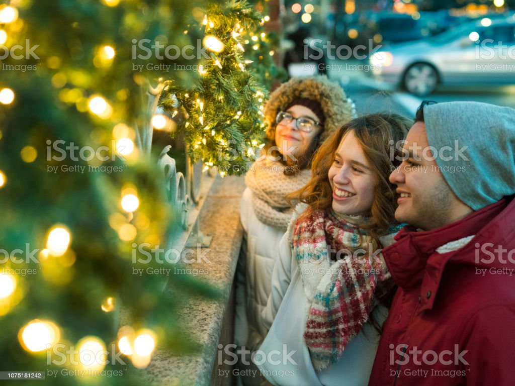 Casal interracial, adolescentes, o bonito caucasiano branco 17 anos de idade menina de cabelos longos e lindo Latino hispânico rapaz de 18 anos de idade e sua amiga, garota adolescente de 15 anos de idade, aproveitando a iluminação de Natal e se diverti - foto de acervo