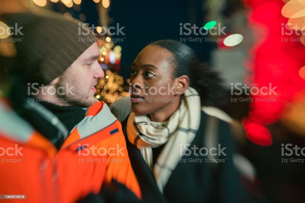 Interracial loving couple, the beautiful Black young woman and handsome young man, watching Christmas Lights and having fun in the cold winter day in Brooklyn, New York. stock photo