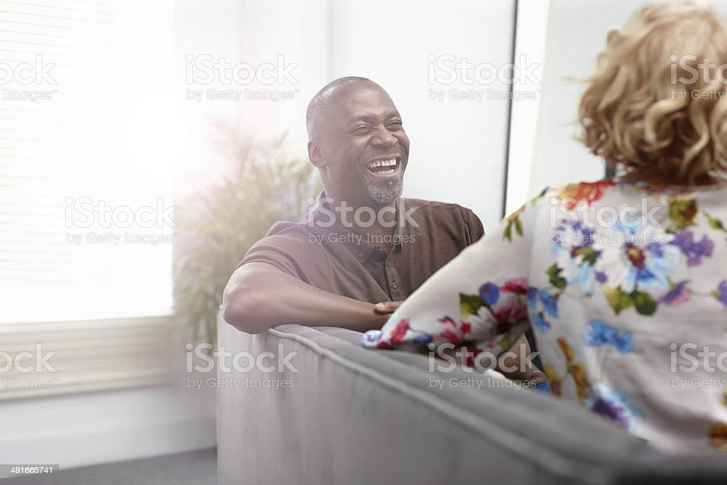 Interracial mature couple having a friendly chat - Indoors stock photo