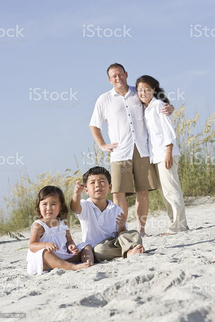 Interracial parents watching young children eating lollipops royalty-free stock photo