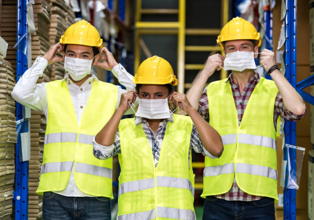 Interracial warehouse worker team putting on  face mask stock photo