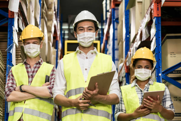 Interracial warehouse worker team with face mask stock photo