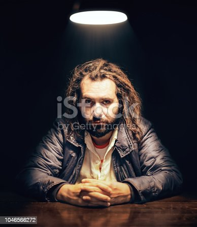 Young serious man sitting under the light in the interrogation room.