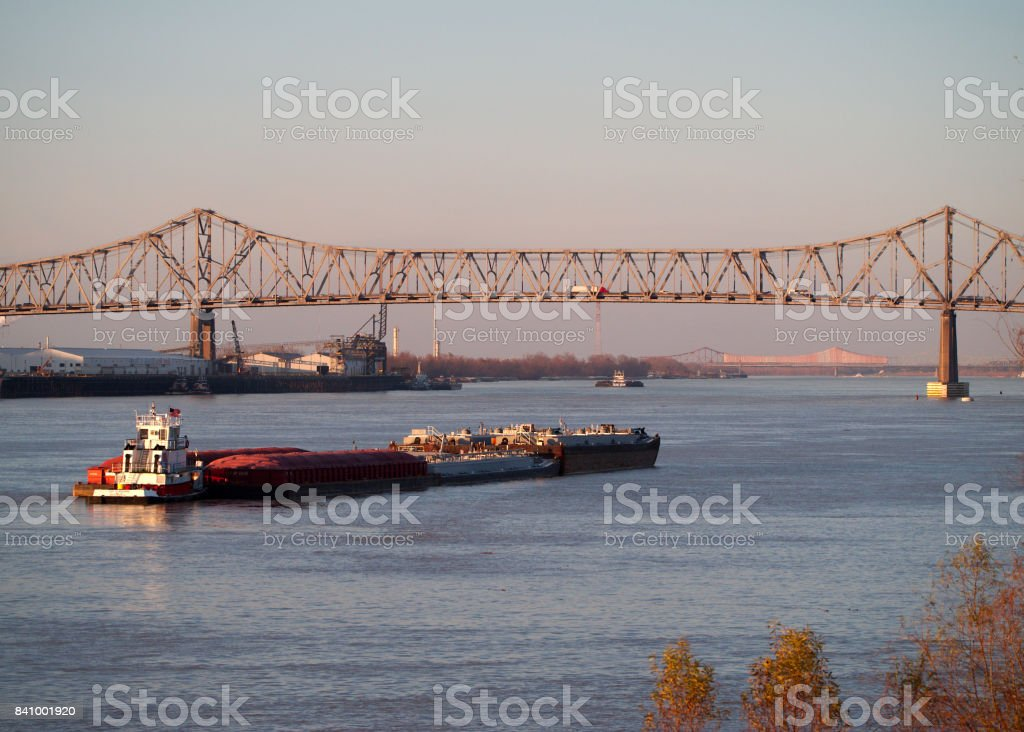 BATON ROUGE, LOUISIANA, USA - 2015: Interstate 10 bridge joining Baton Rouge and Port Allen across the Mississippi river in Louisiana, with a barge in the foreground. stock photo