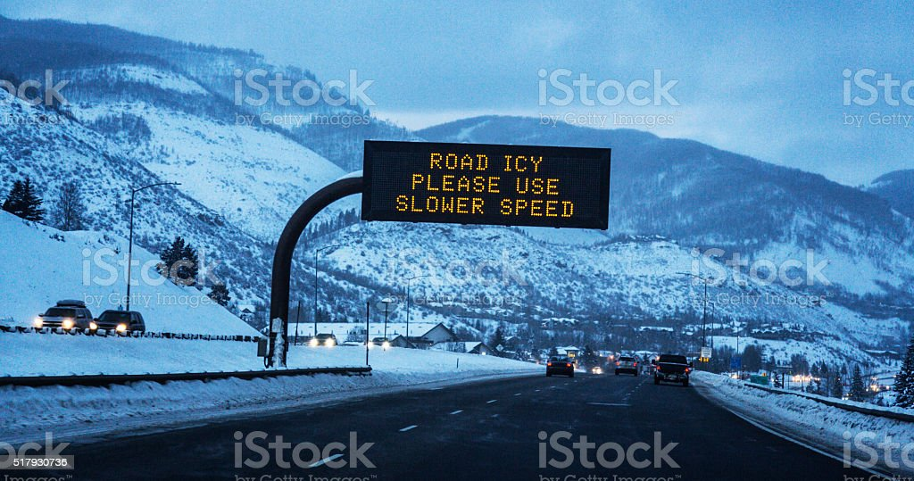 ROAD ICY SLOW DOWN Interstate 70 Road Sign Vail Colorado stock photo