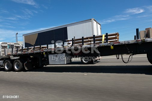 Semi s, flatbeds, and trailers on the Interstate highway. Horizontal.
