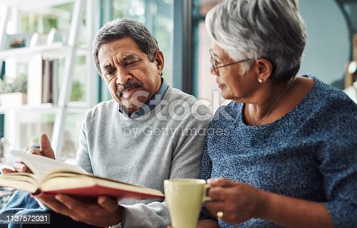 Cropped shot of a relaxed elderly couple reading from the bible while drinking coffee at home during the day