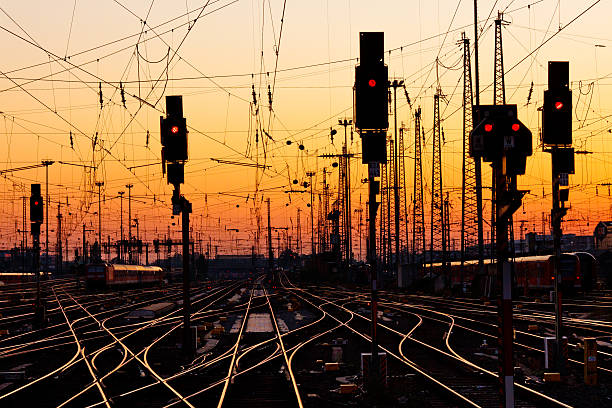 Intertwined railroad tracks with traffic lights at sunset stock photo