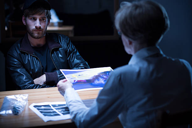 Interview in interrogation room Suspect man interview in dark interrogation room police interview stock pictures, royalty-free photos & images