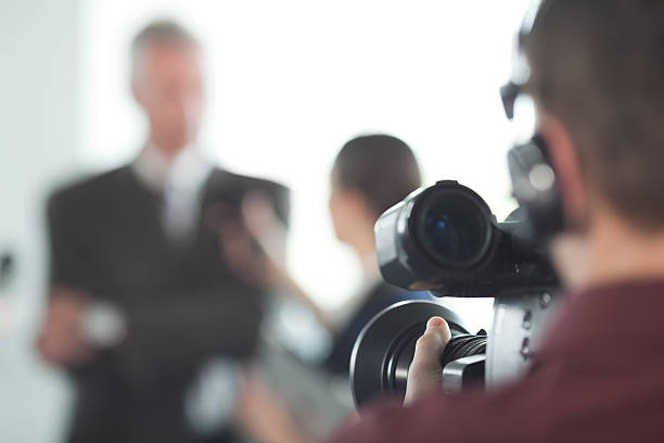 Interview. Video operator broadcasting an interview with people in background. spokesperson stock pictures, royalty-free photos & images