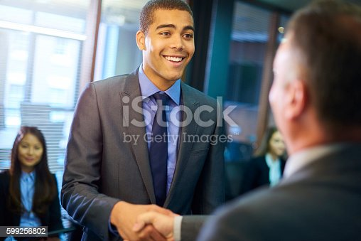 young man steps forward as he is called in for his interview and shakes hands with his possible new employer.
