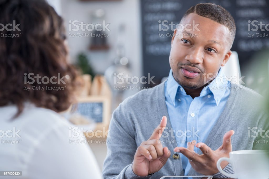 Interviewer outlines job responsibilities during coffee shop interview stock photo
