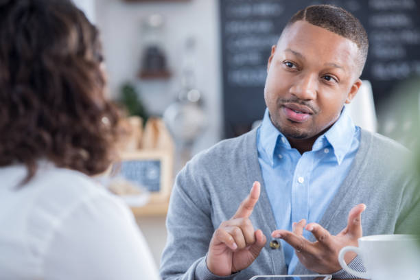 interviewer outlines job responsibilities during coffee shop interview - disdainful stock pictures, royalty-free photos & images