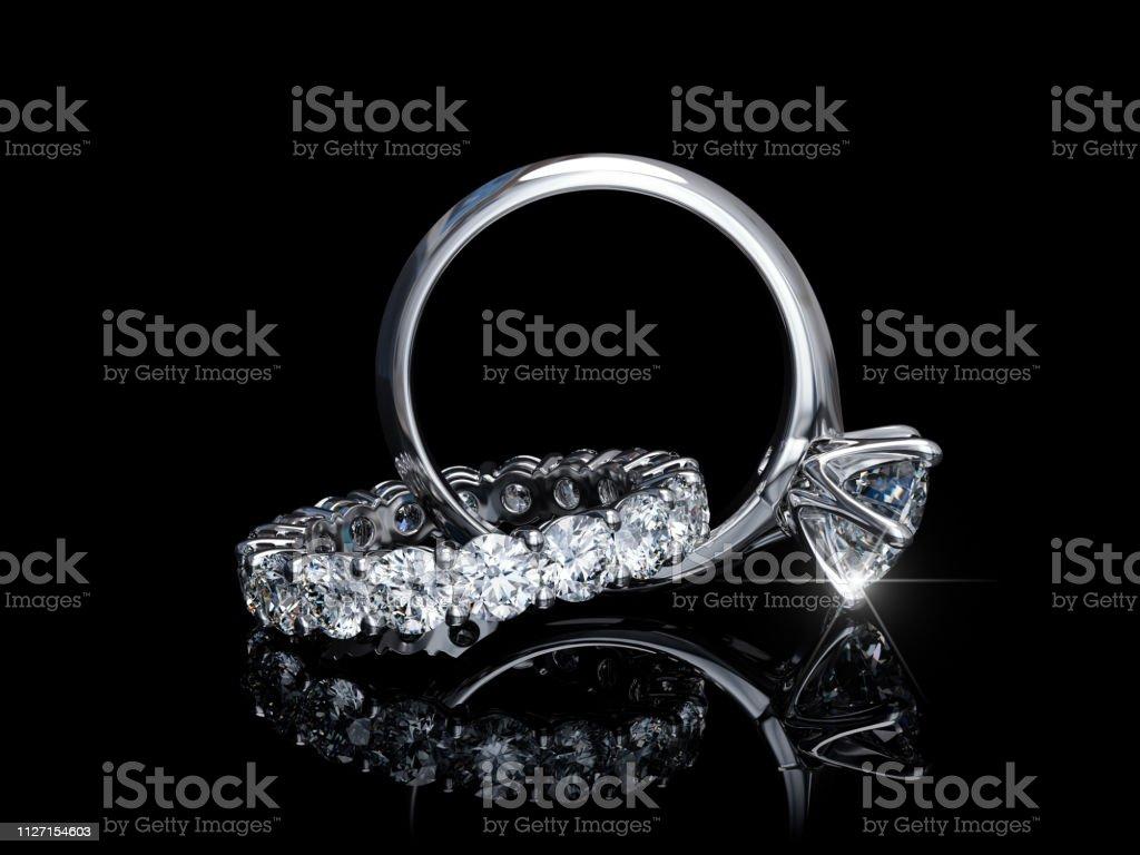 Interwoven diamond engagement ring, wedding ring on black background - Zbiór zdjęć royalty-free (Bez ludzi)