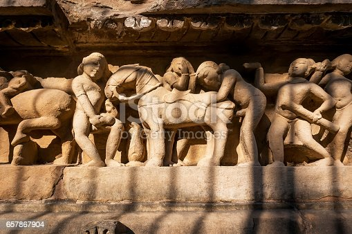 istock Intimate life of ancient people on stone relief on wall of Khajuraho temple, India. 657867904