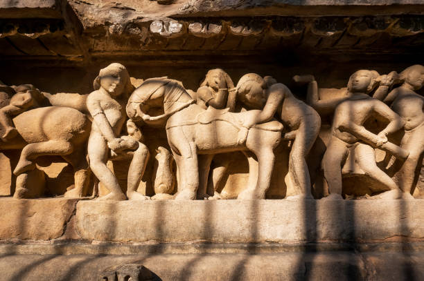 Intimate life of ancient people on stone relief on wall of Khajuraho temple, India. stock photo