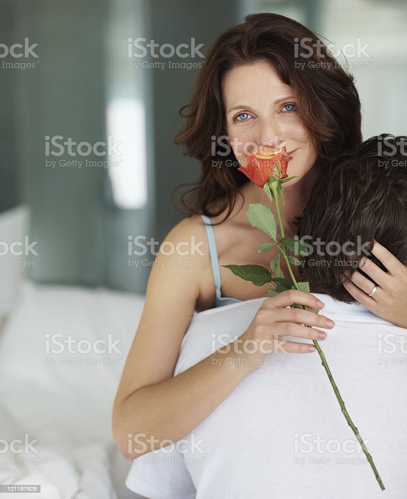 Intimate woman holding rose in bed with husband royalty-free stock photo