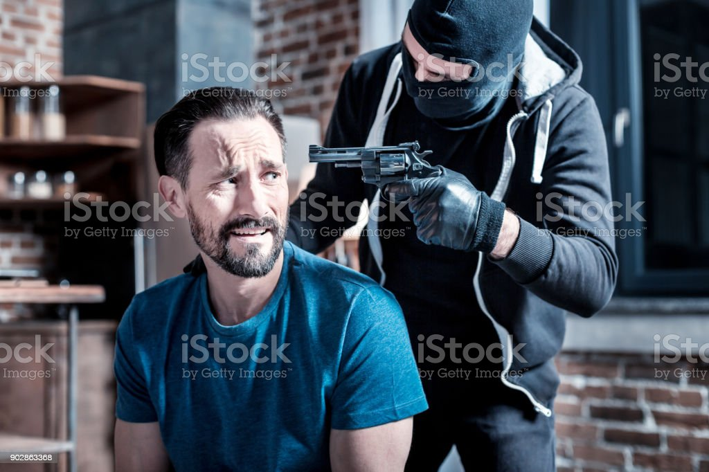 Homem intimidado e um criminoso com uma pistola - foto de acervo