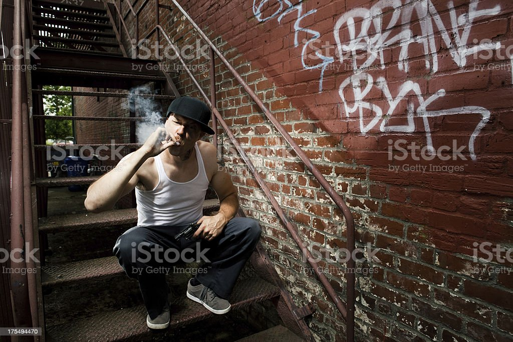 Intimidating Caucasian Criminal and Gangster Smoking a Cigarette in Alley stock photo