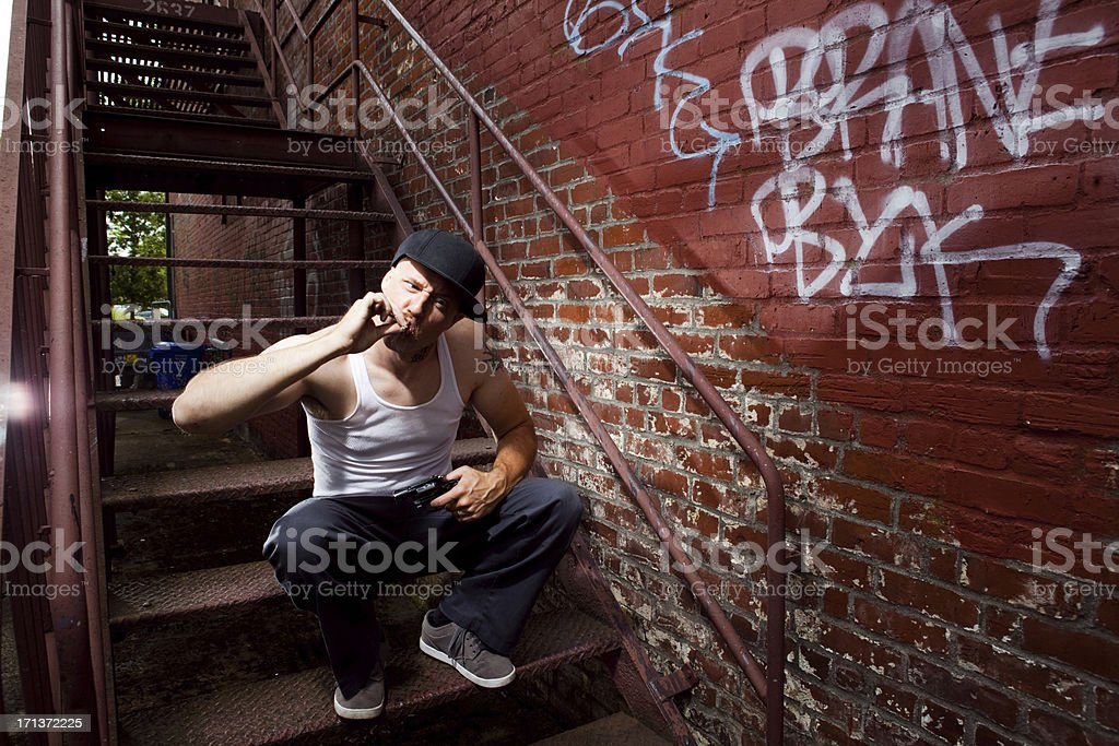 Intimidating White Criminal and Gangster Smoking a Joint in Alley stock photo