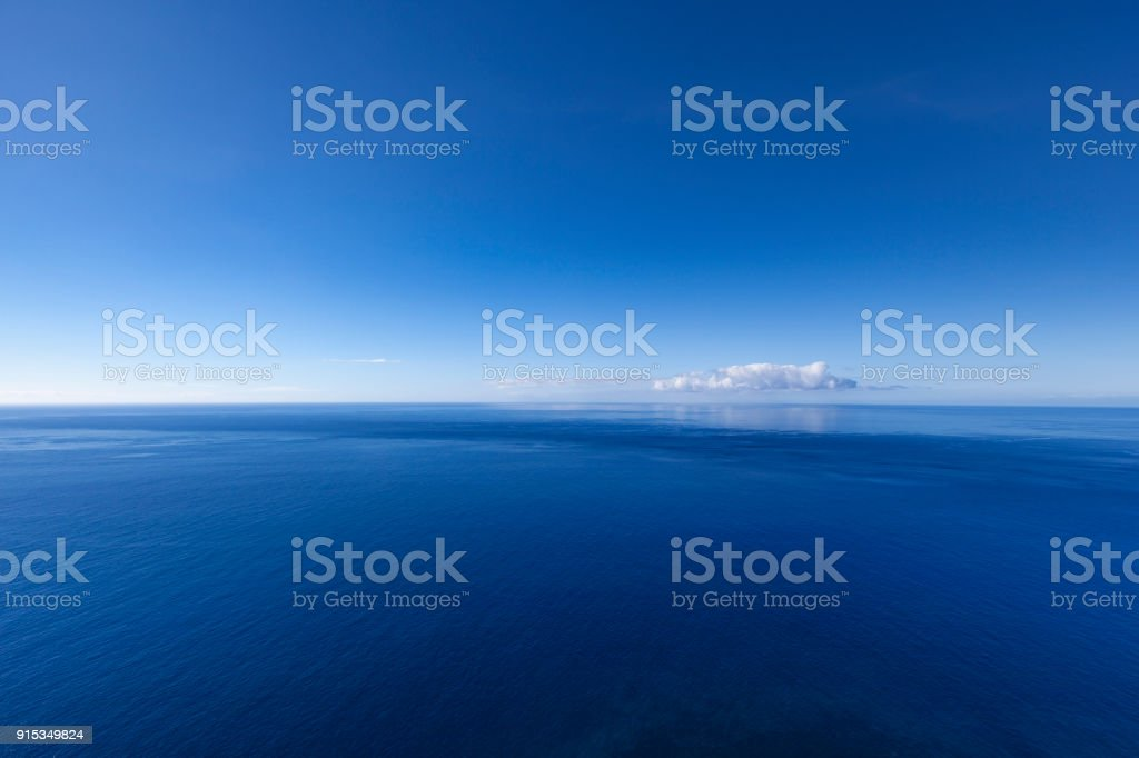 into the blue, ocean seascape with lonely cloud stock photo