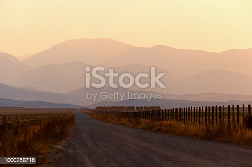 A lonely dirt road heads toward distant hazy mountains in Montana.