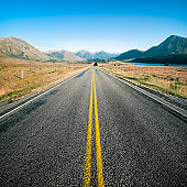 An empty long and straight country road on New Zealand's South Island.