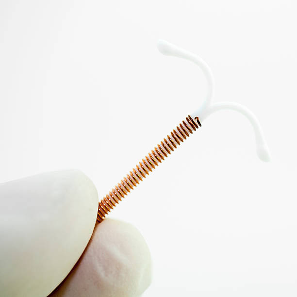 Intrauterine device IT-shaped plastic device that is wrapped in copper or contains hormones.  iud stock pictures, royalty-free photos & images