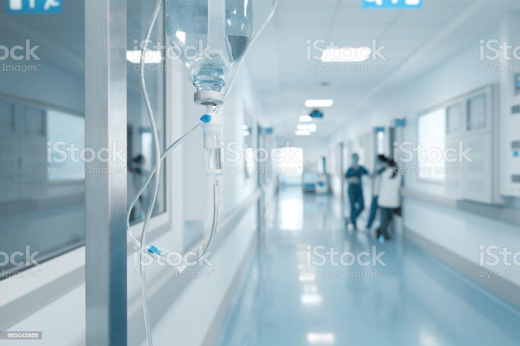 Die Infusion auf dem Gestell auf dem Hintergrund der Krankenschwestern in den krankenhausflur im Gespräch – Foto