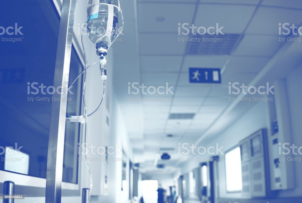 Intravenous system in the hospital hallway with blurred person afar royalty-free stock photo