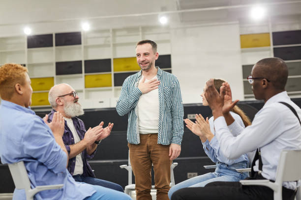 Introduction at Support Group Meeting Portrait of smiling mature man    introducing himself during therapy session in support group to people clapping, copy space dependency stock pictures, royalty-free photos & images