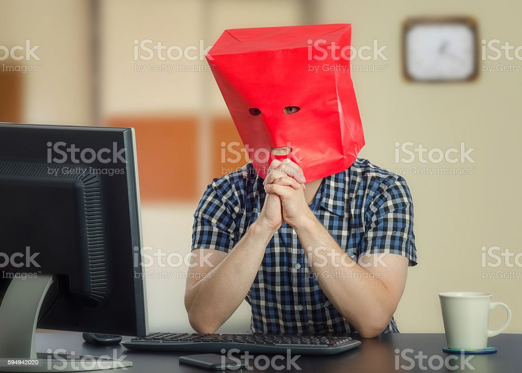 Introverted young man in red paper bag stock photo