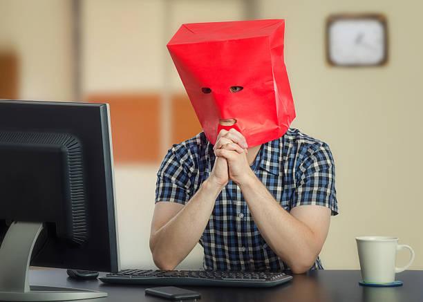 introverted young man in red paper bag - rot bekümmerte möbel stock-fotos und bilder