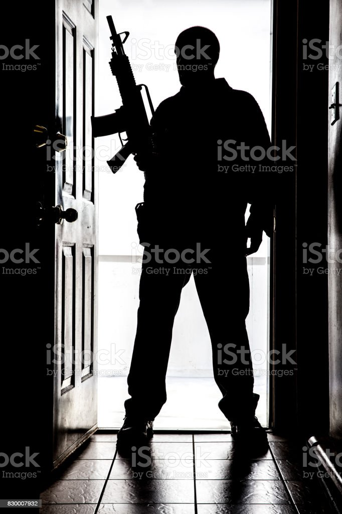 Intruder at door, in silhouette with AR-15 style long gun stock photo