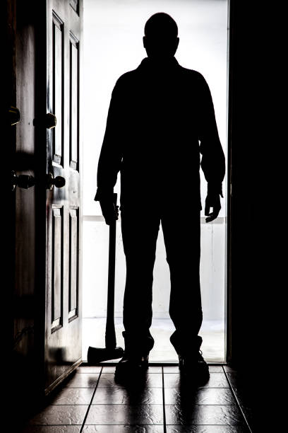 intruder at door, in silhouette with axe - killer stock photos and pictures